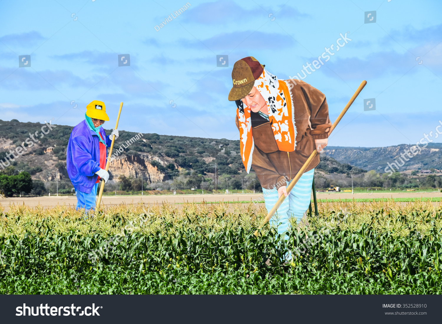 """Salinas, California, USA - September 2, 2015: Giant cut out figures of farm workers tend to the corn fields along the roadside in the Salinas Valley (Monterey County), """"the salad bowl of the world""""."""