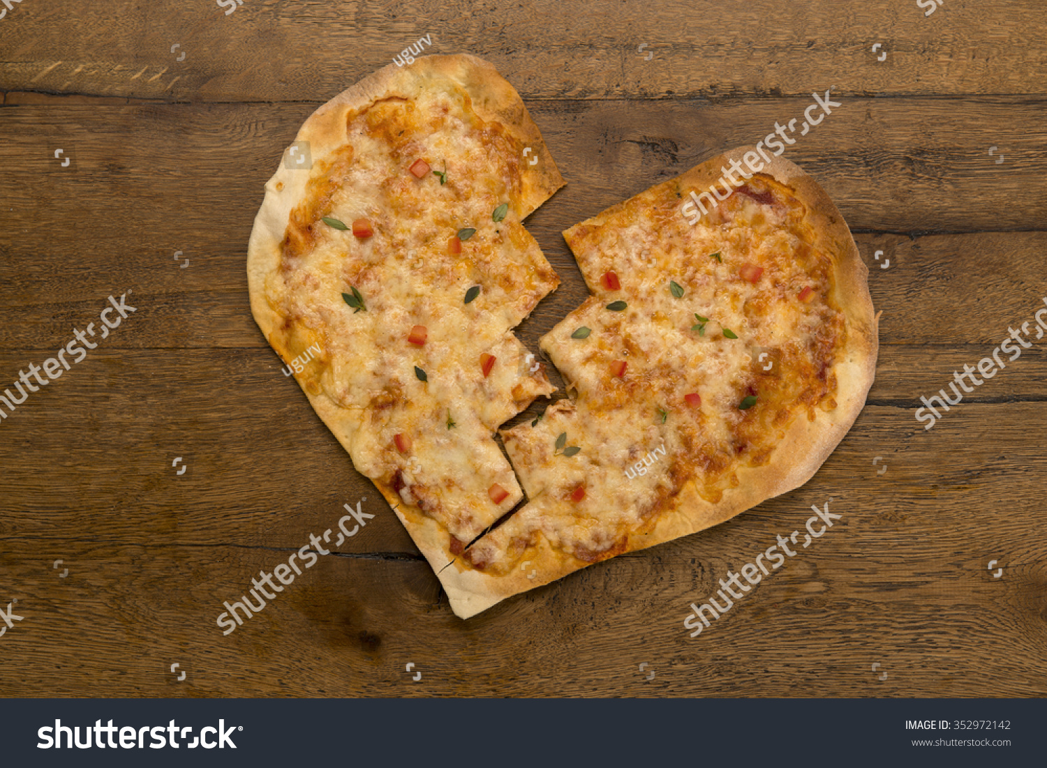 Broken Heart Shaped Valentines Pizza On A Wooden Table.