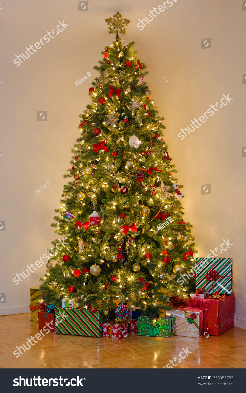 Decorated pine tree many presents under stock photo for Red and yellow christmas tree
