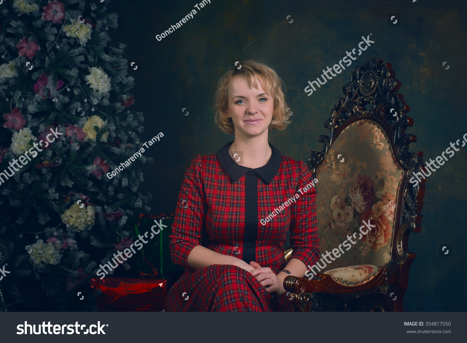 Girl in retro vintage dress sitting in the chair next to the Christmas tree