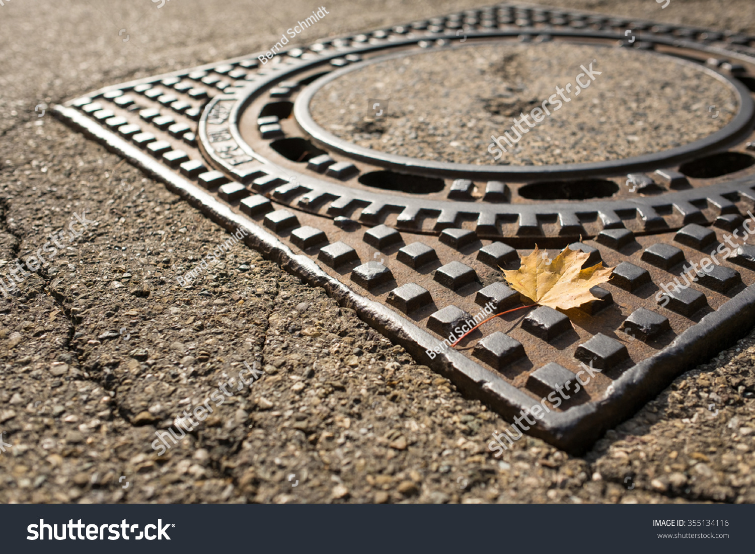 Yellow Maple Leaf On A Manhole Cover Of Steel Stock Photo ...