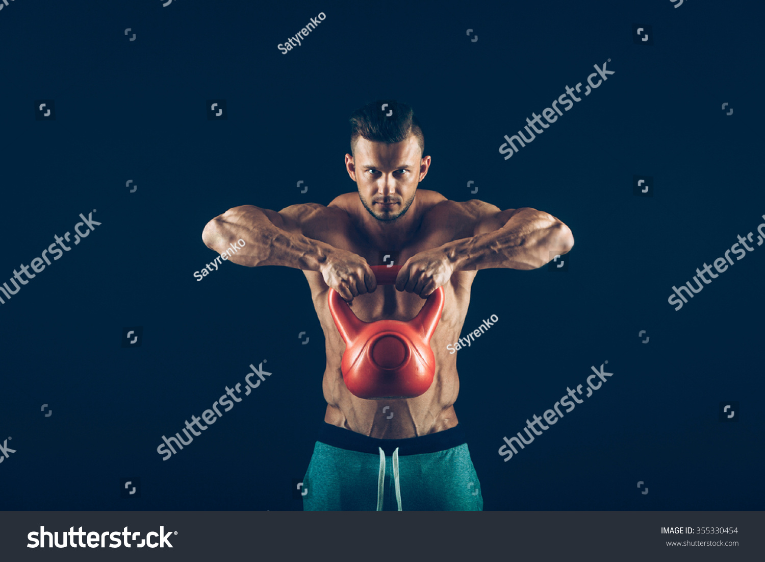 Fitness man doing a weight training by lifting a heavy kettlebell