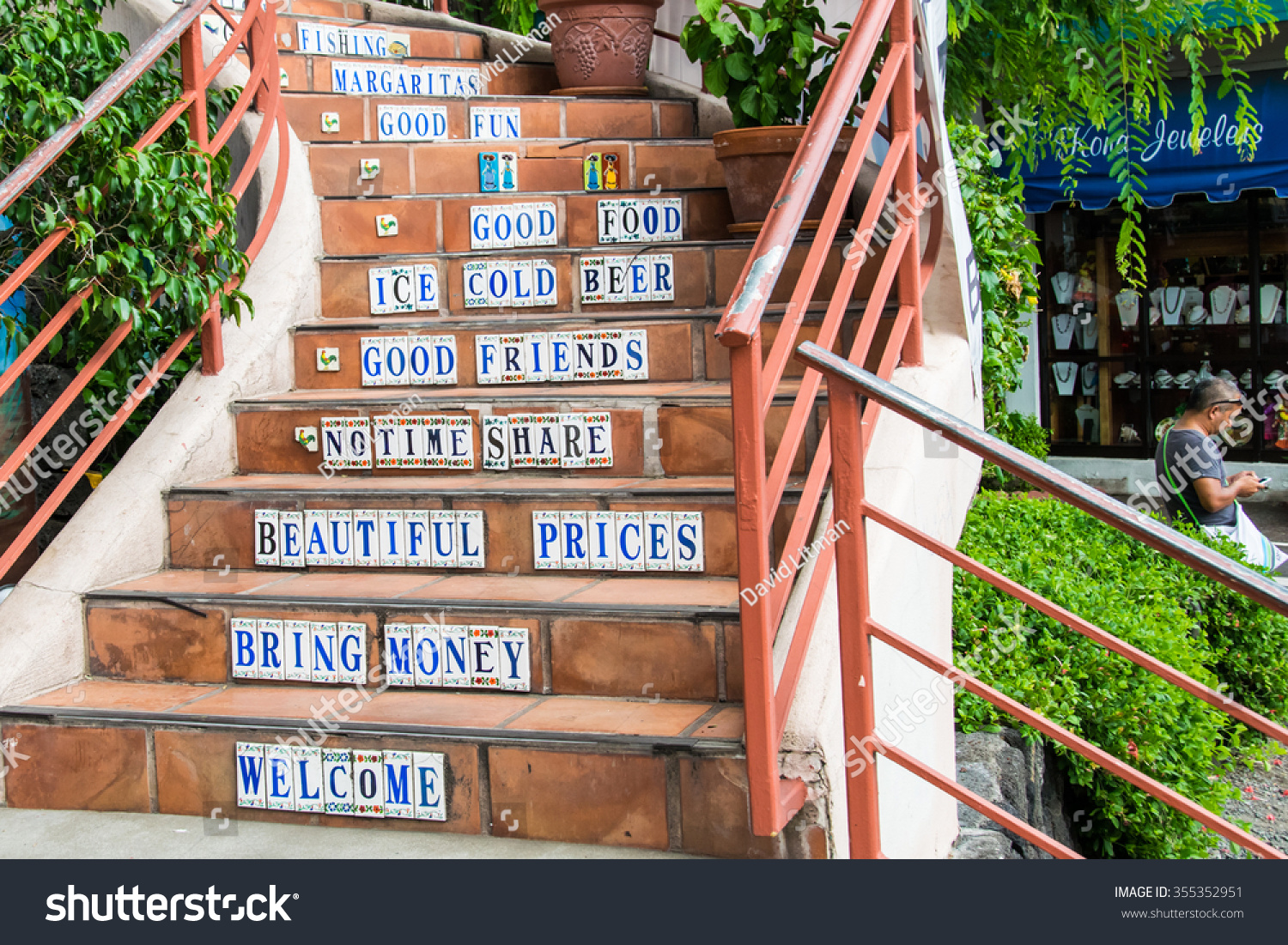 "Kailua, Hawaii, the Big Island - October 8, 2015: A stairwell leading to a restaurant bar has slogans including ""welcome"",  ""bring money"", ""beautiful prices"", ""no time share"", ""good food"", ""good fun"""