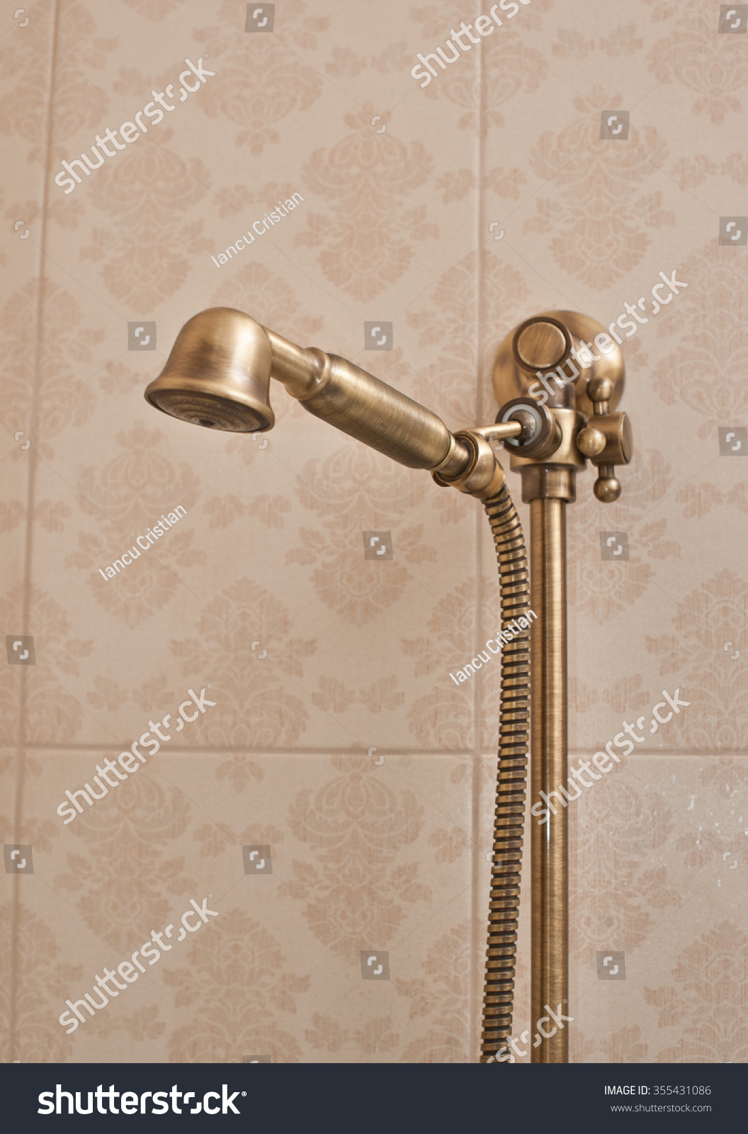 golden shower head on wall with faience vintage shower head