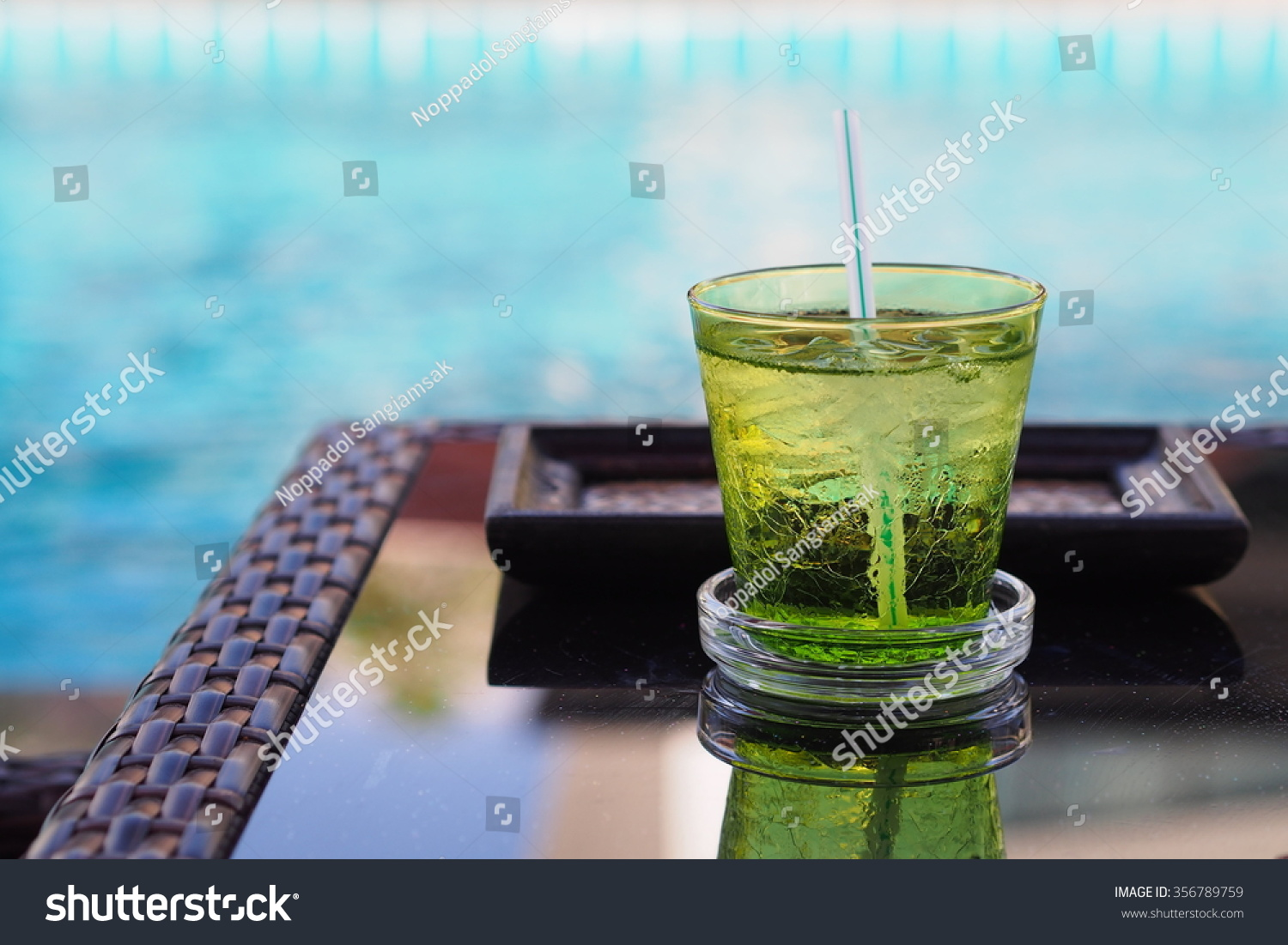 A green glass of drinking water on a table beside swimming pool stock photo 356789759 shutterstock How to make swimming pool water drinkable