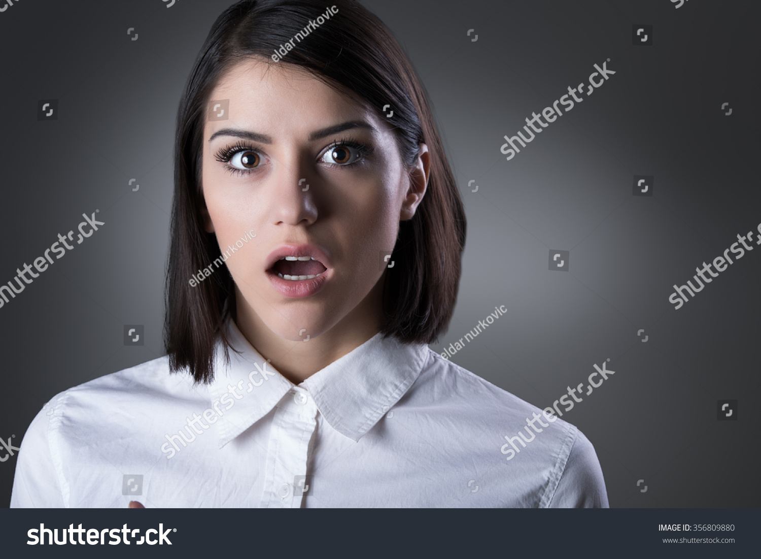 Young Woman Pointing And Looking Surprised Stock Photo