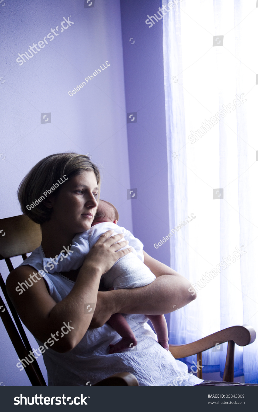 Mother rocking newborn baby rocking chair stock photo for Chair next to window