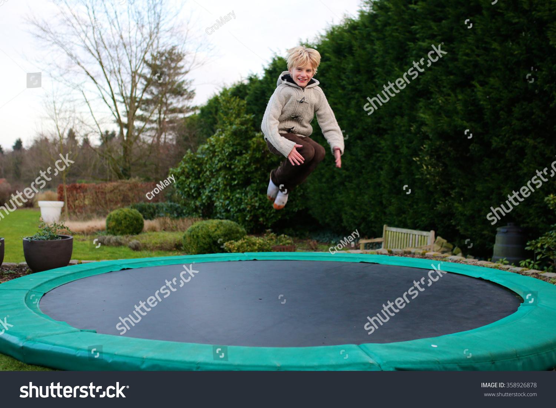 Happy Kid Plays Outdoors Garden Jumping Stock