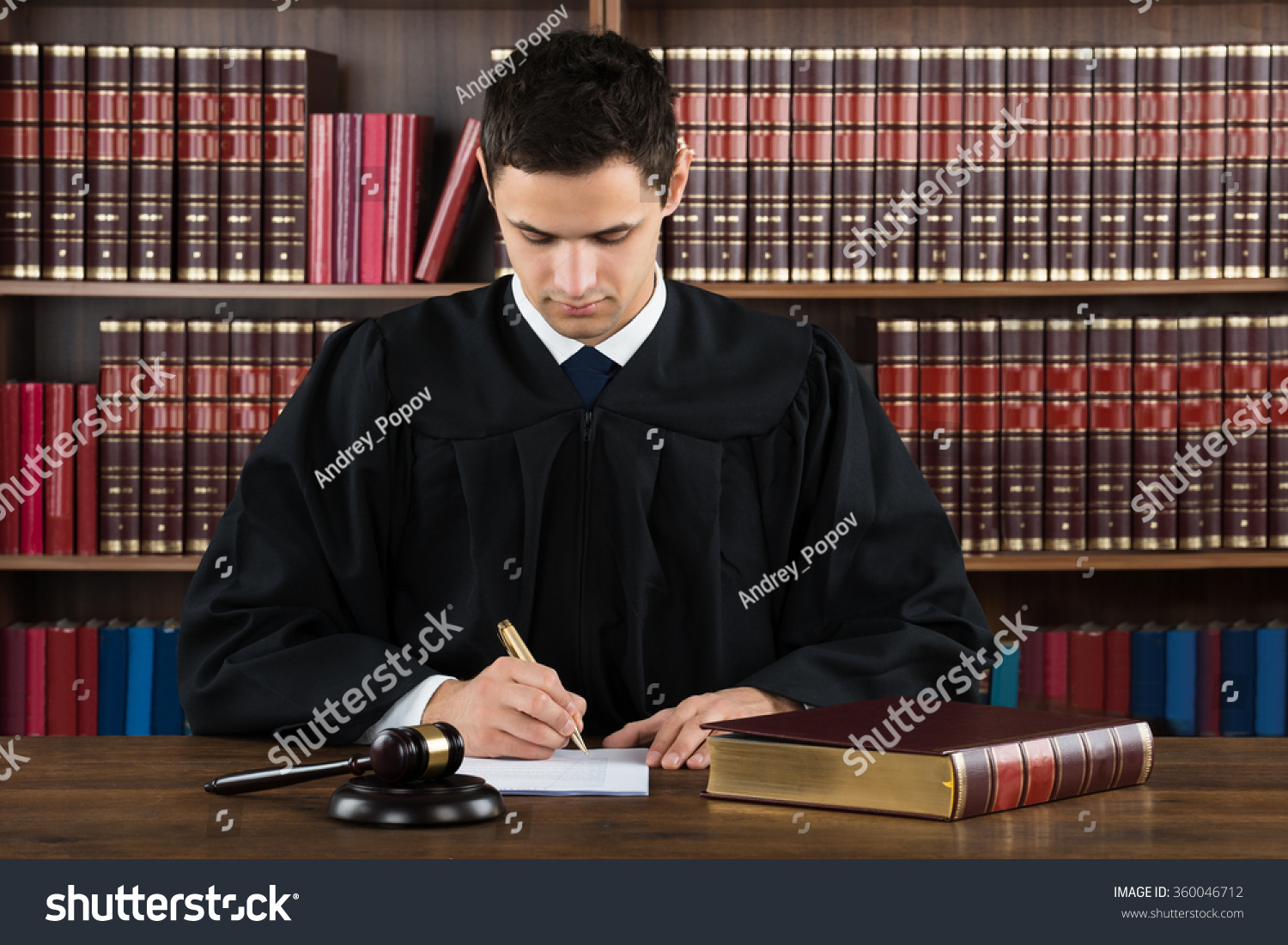 Young Male Judge Making Legal Documents At Desk Against Bookshelf In Courtroom
