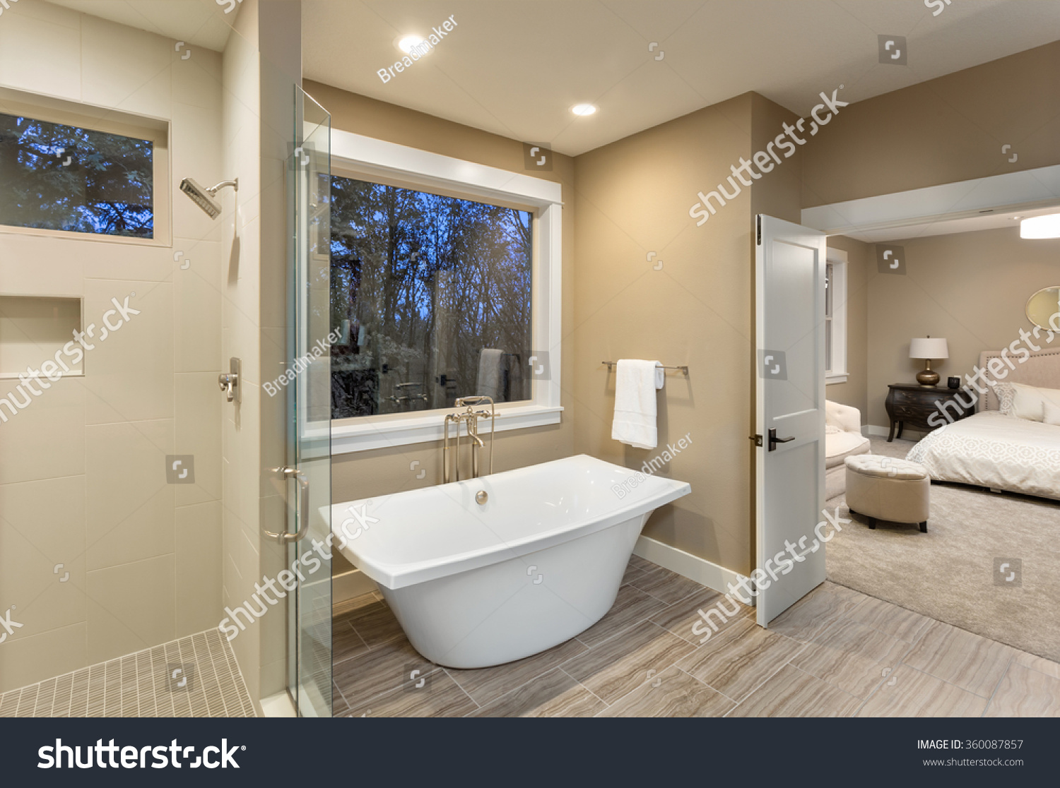 large furnished bathroom in luxury home with tile floor shower bathtub and view