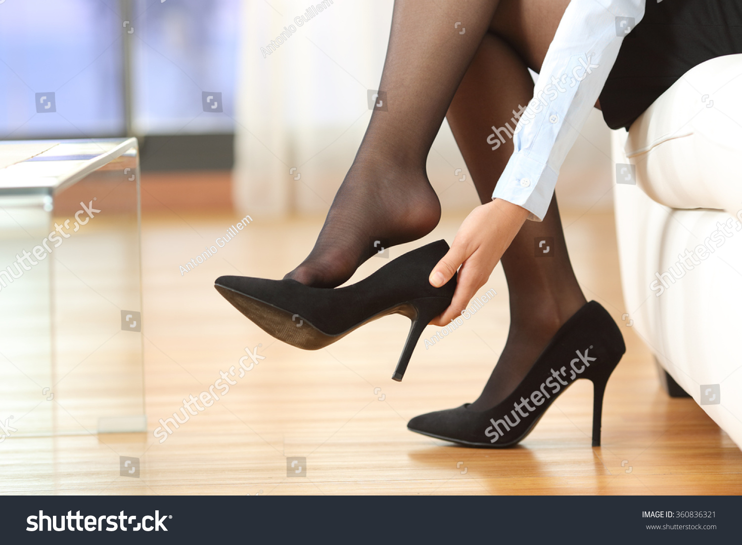 Businesswoman taking off high heels shoes after work at home #360836321