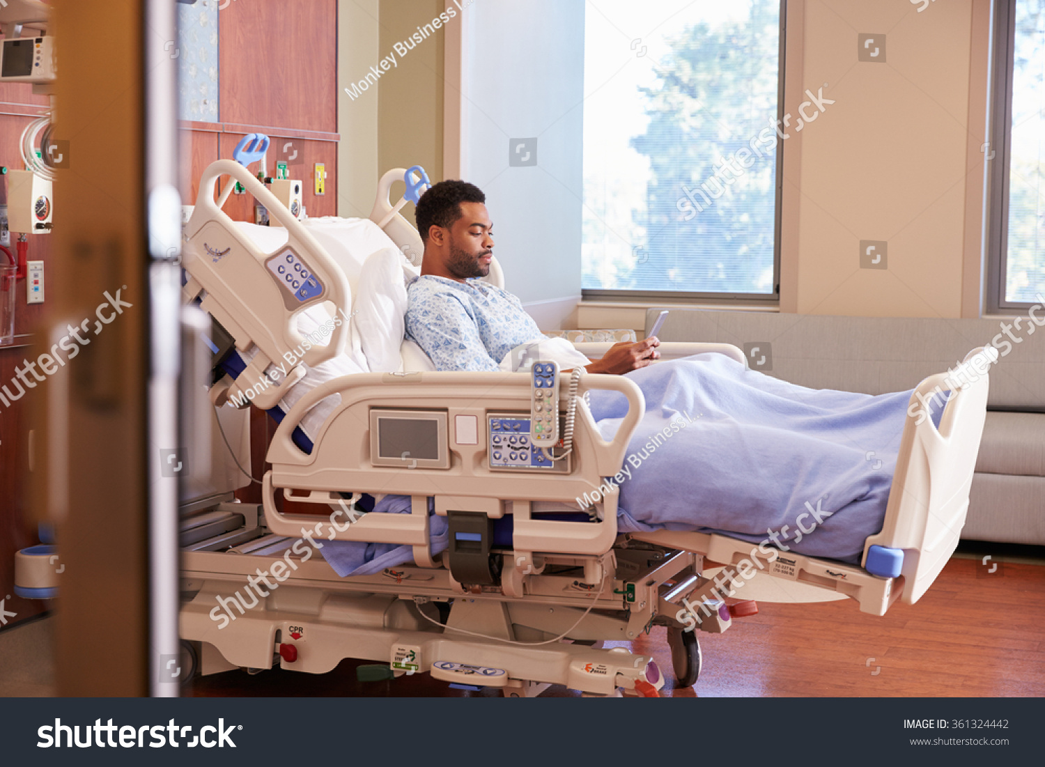 male patient hospital bed using cellphone stock photo