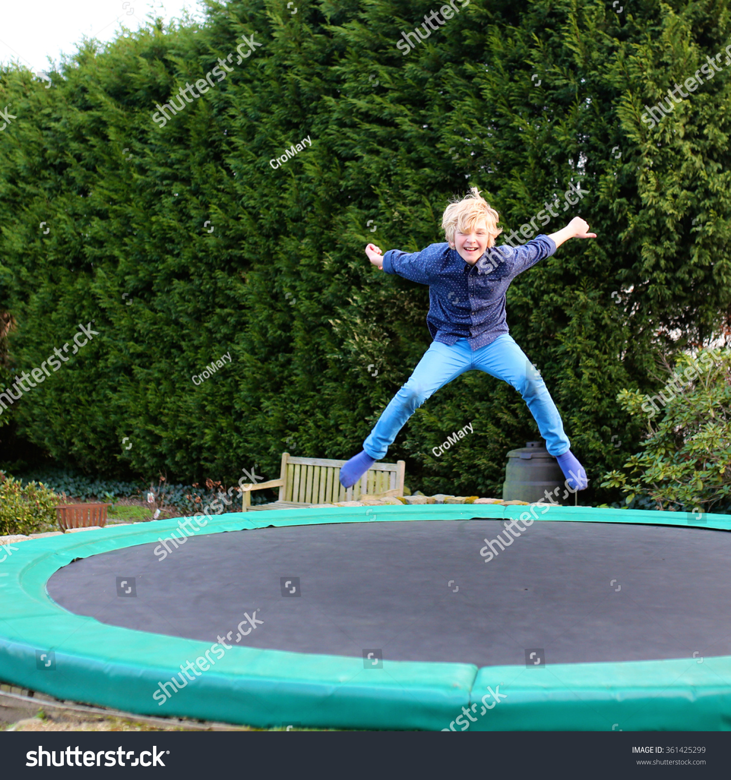 Springs Trampoline Park Waiver: Happy Kid Plays Outdoors Garden Jumping Stock Photo