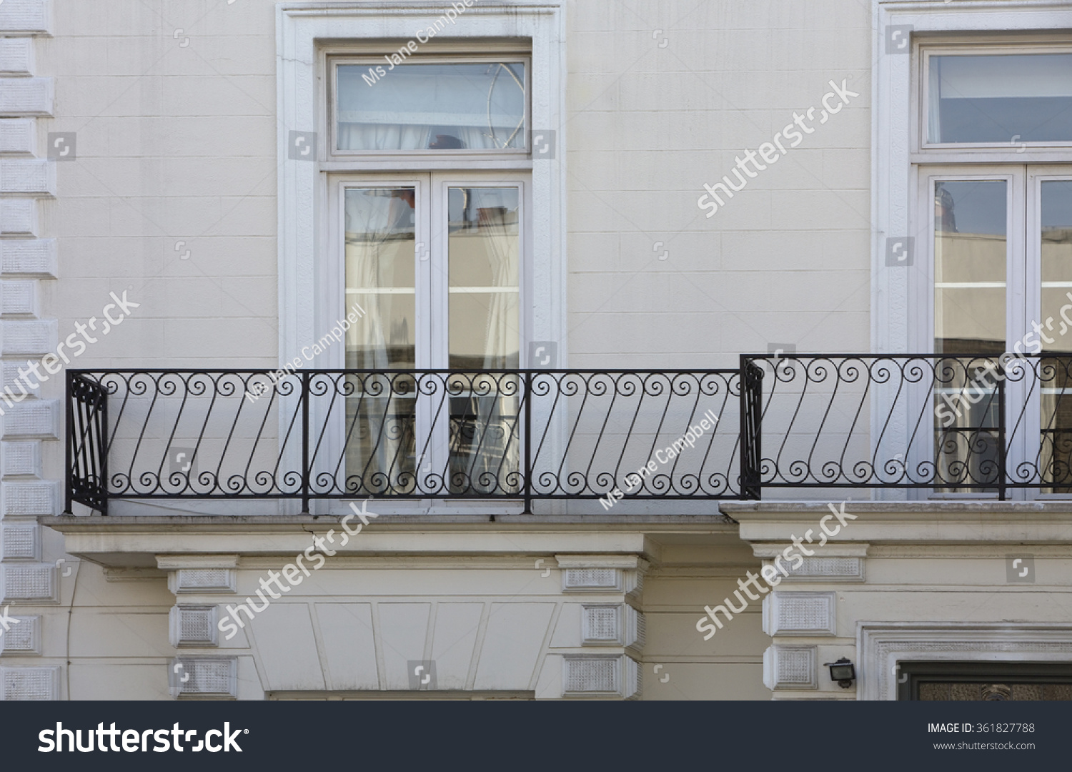 Wrought iron railing a repeating simple pattern sets up an image of elegance on this