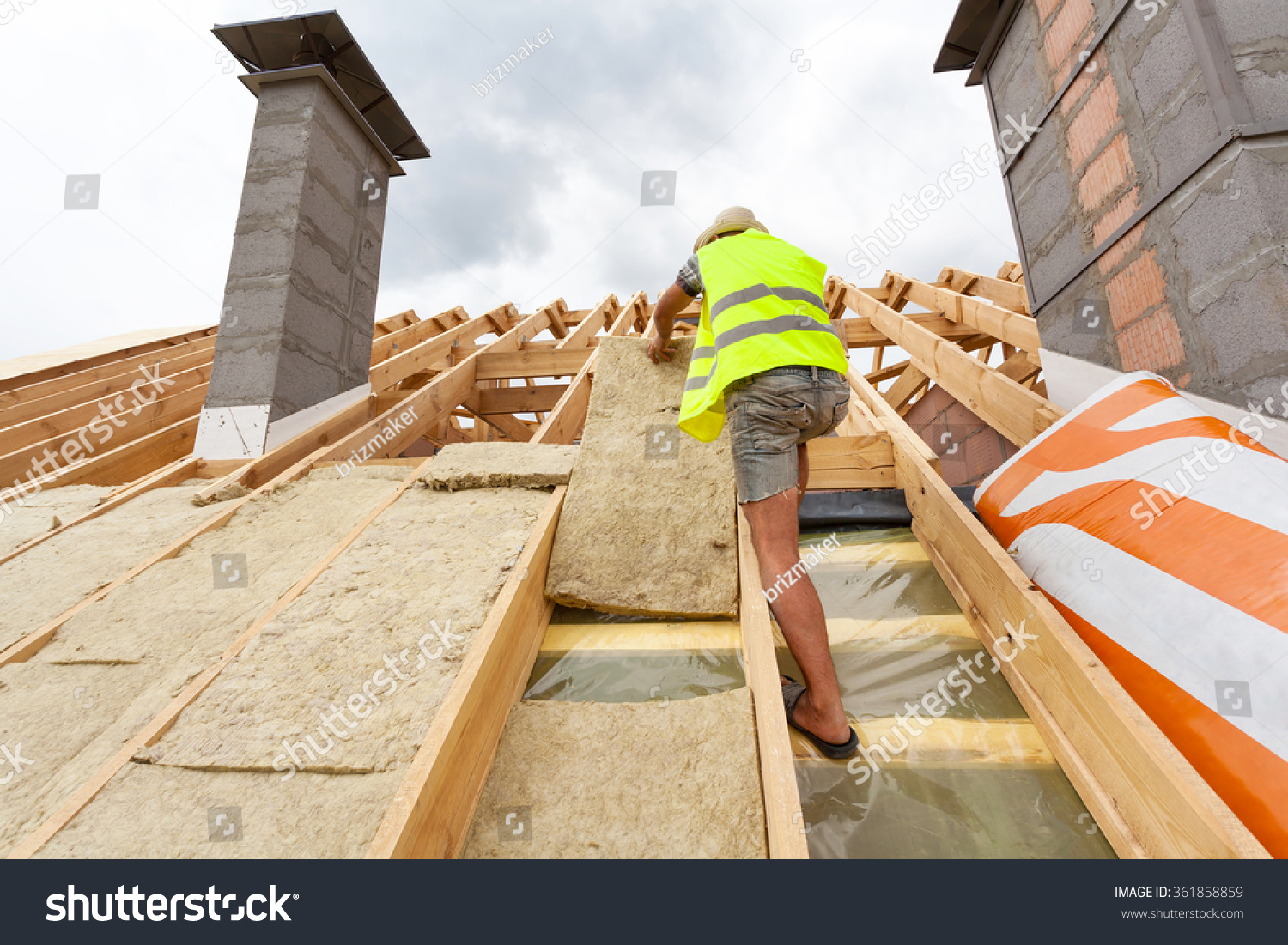 Roofer builder worker installing roof insulation stock for New home insulation