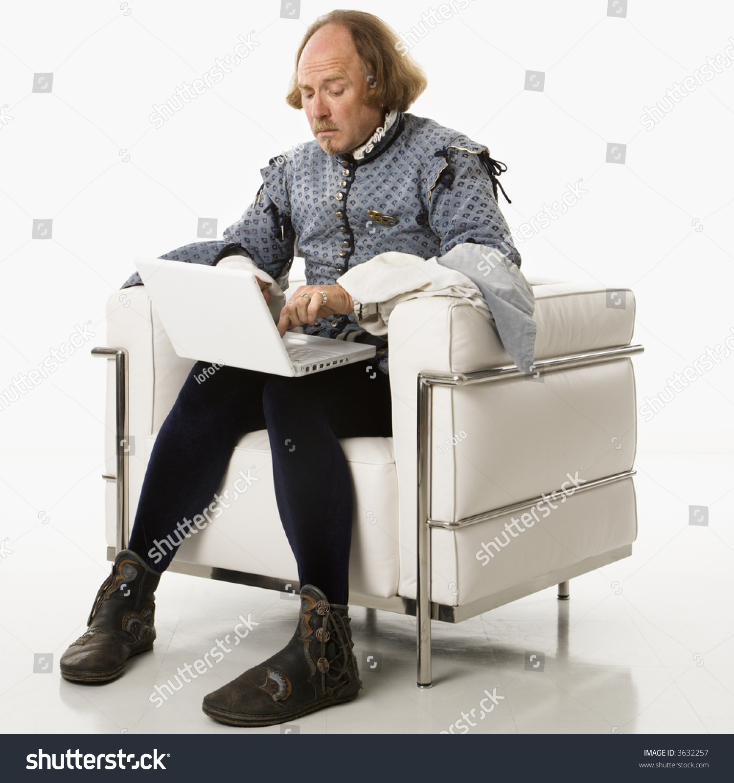 william shakespeare period clothing sitting on stock photo  william shakespeare in period clothing sitting on modern chair using laptop