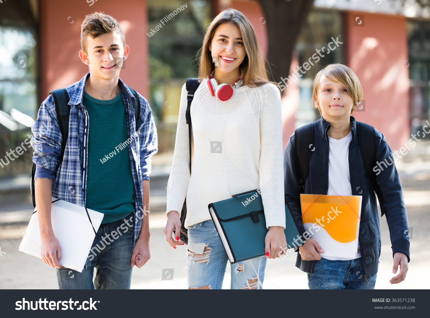 Group Of Caucasian Teens Going To School With Papers For Study ...