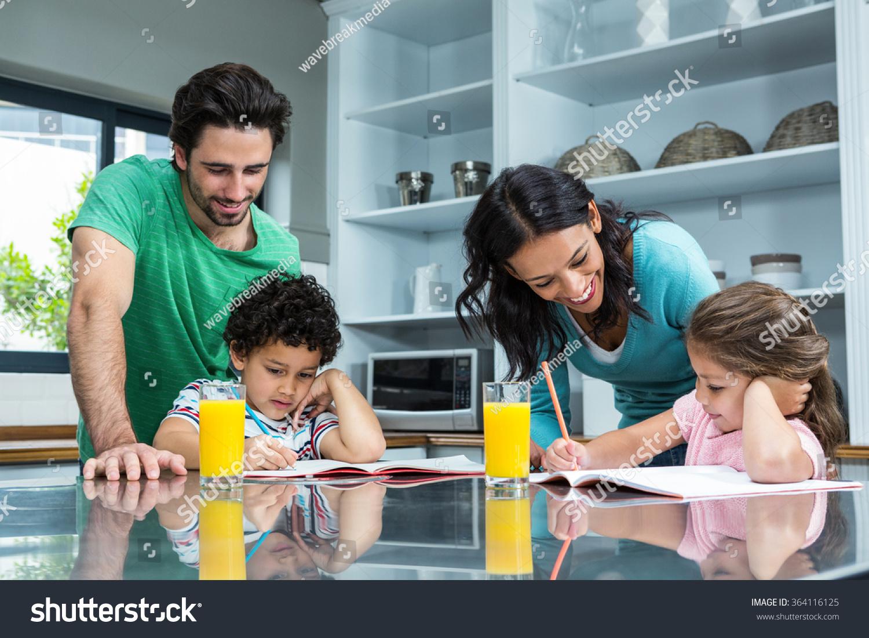 parents helping their children doing homework stock photo