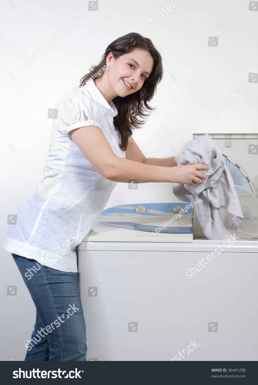Woman Putting Clothes In Washing Machine Close Up Stock