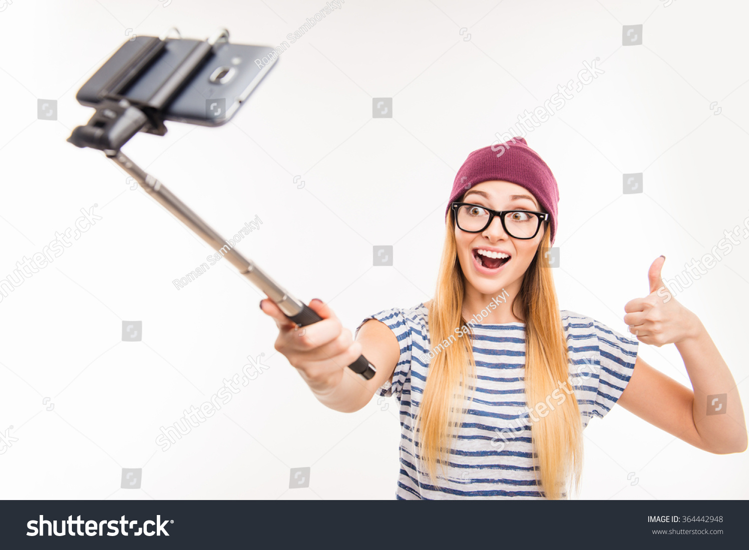 happy girl in cap and glasses making photo by selfie stick and thumbs up 364442948 shutterstock. Black Bedroom Furniture Sets. Home Design Ideas