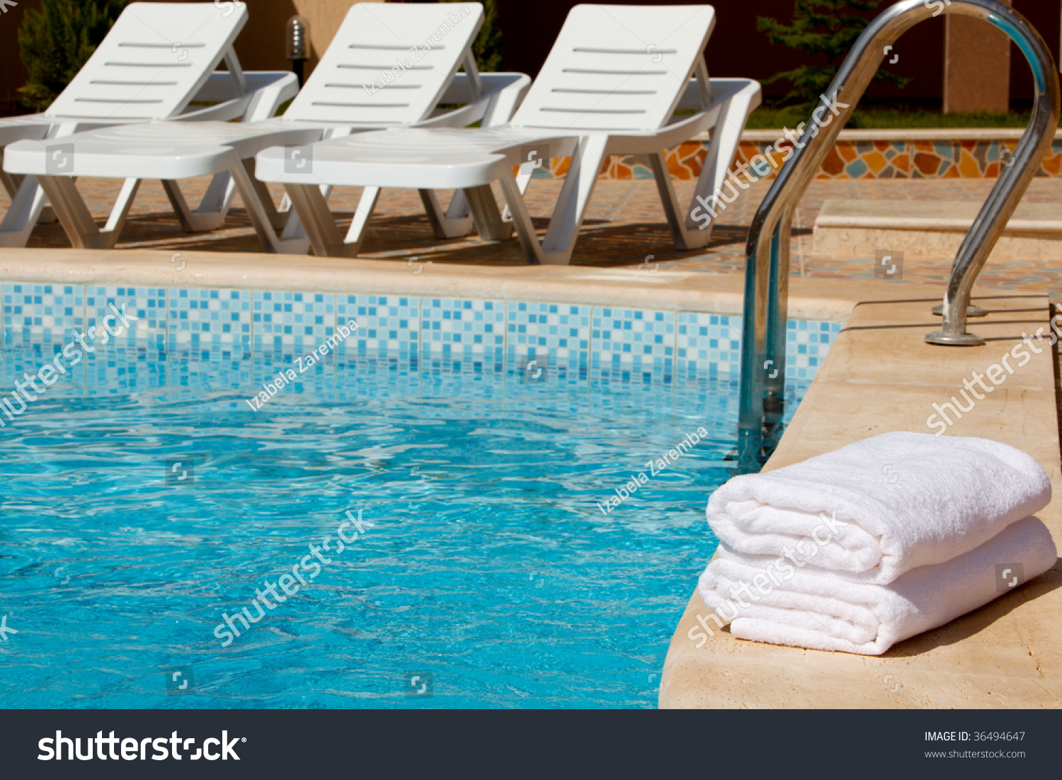 White Pool Deck Chairs: White Towels By The Pool With Deck Chairs In The Back