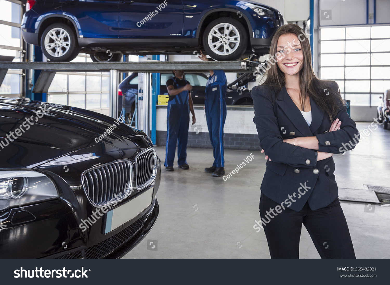 Happy customer in garage with her repaired car in the for Garage happy car