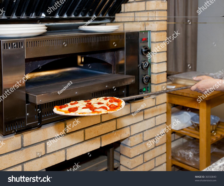 Pizza Restaurant Kitchen man inserting pizza in oven, restaurant kitchen stock photo