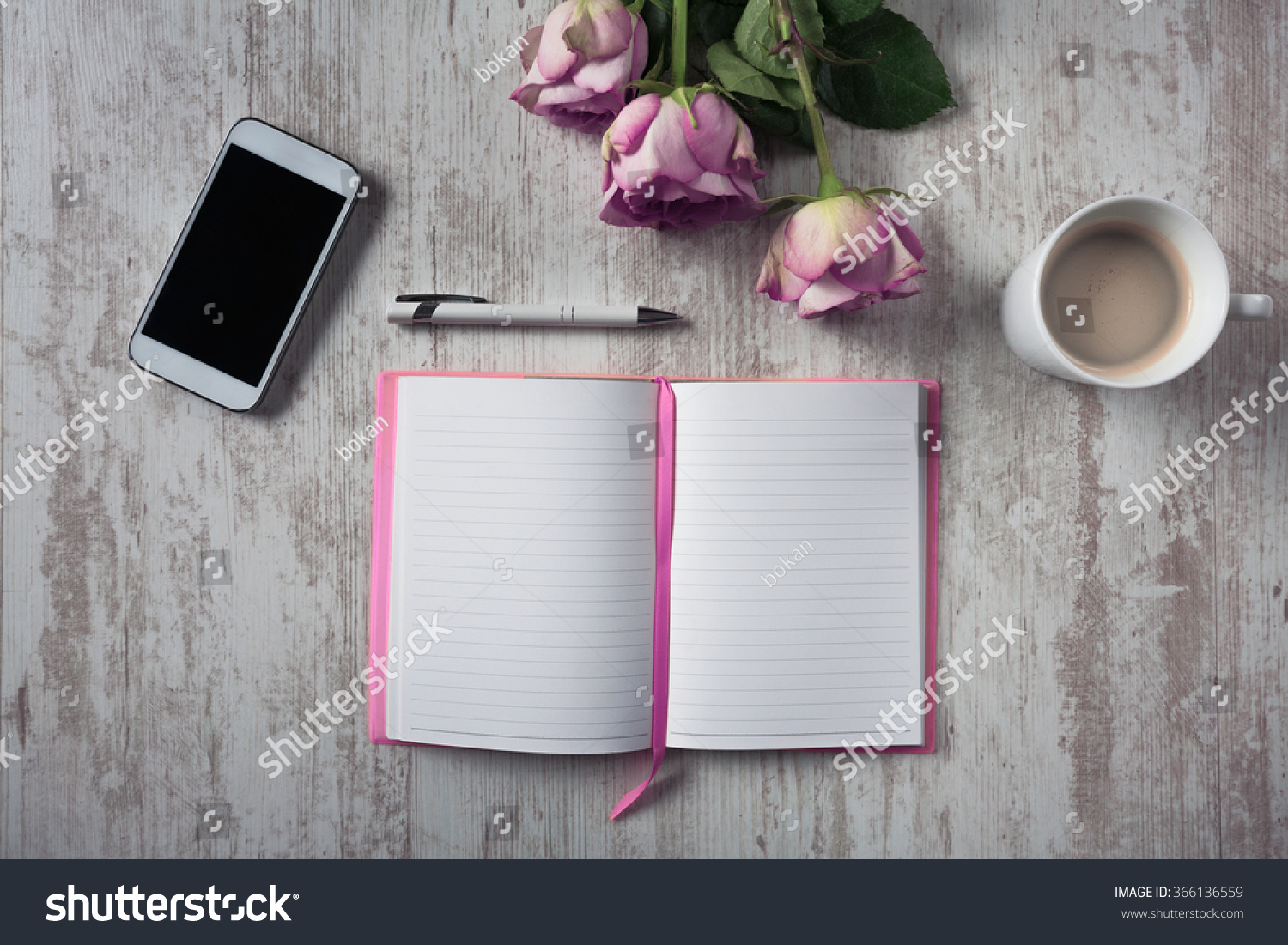 High angle view of open empty notebook mobile phone cup of coffee and bouquet of roses on white wooden table