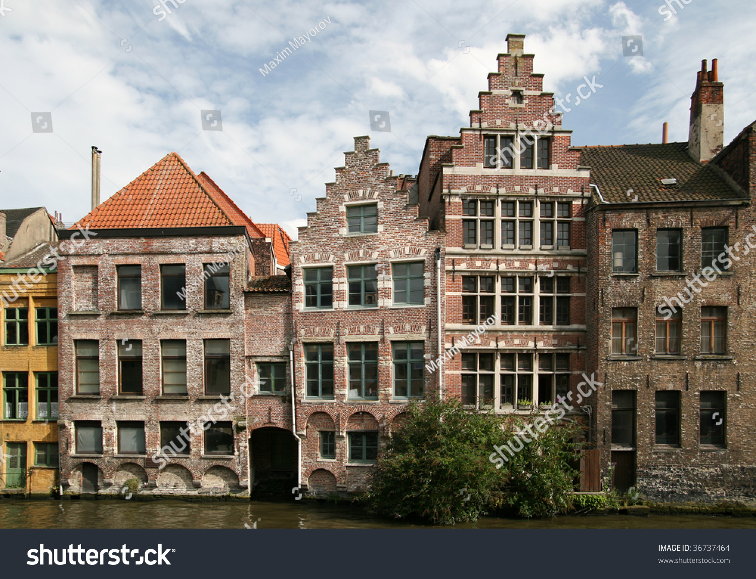 Uneven Traditional European Brick Houses On The Bank Of