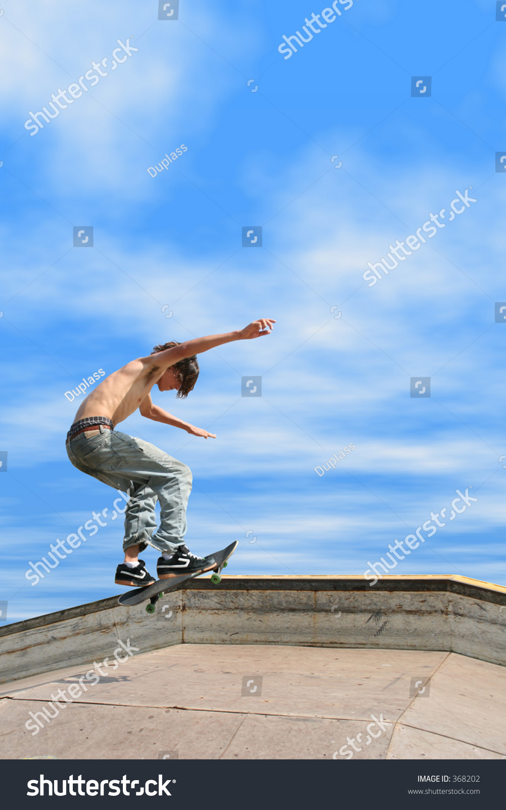 teen boy shirtless jeans skateboarding outdoor stock photo