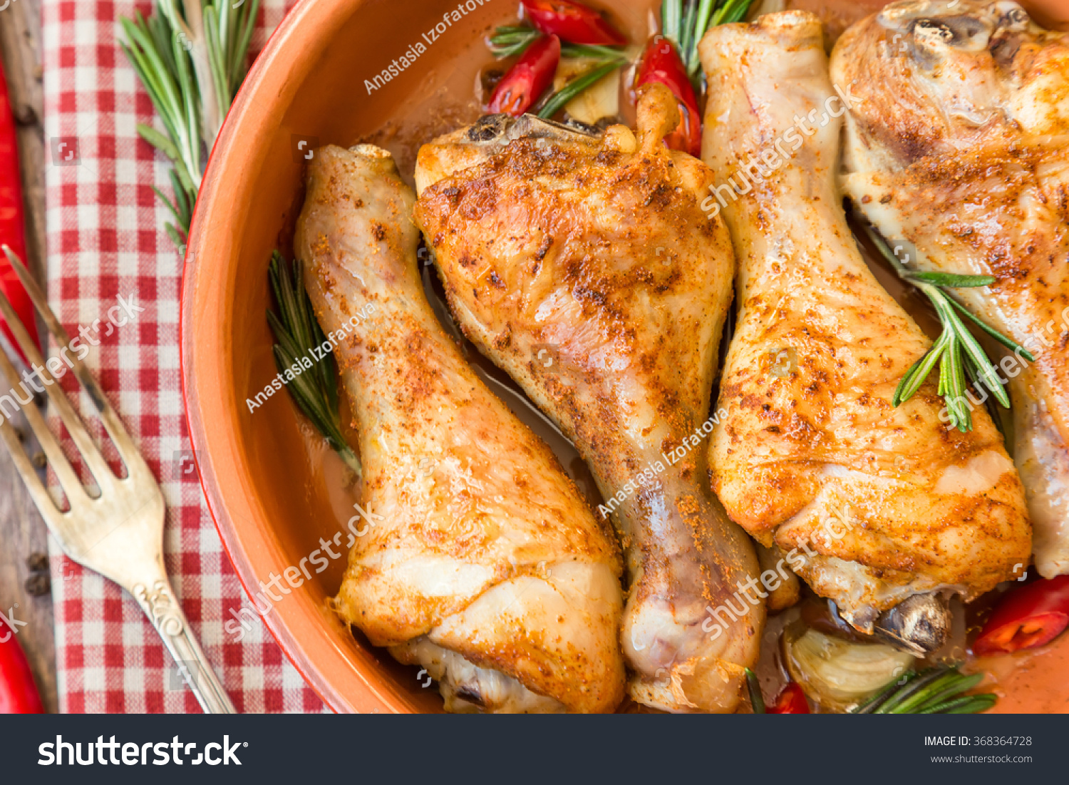 Roasted chicken legs with rosemary, garlic and red chili pepper on ...