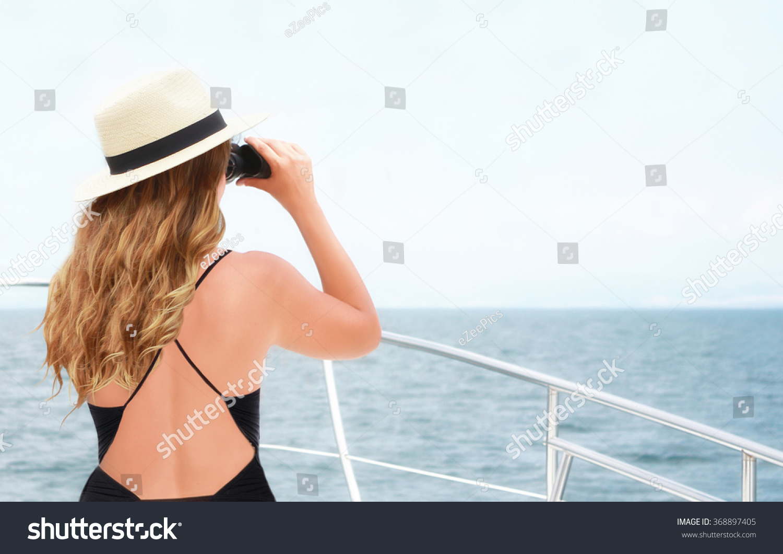 bikini woman with binoculars on boat