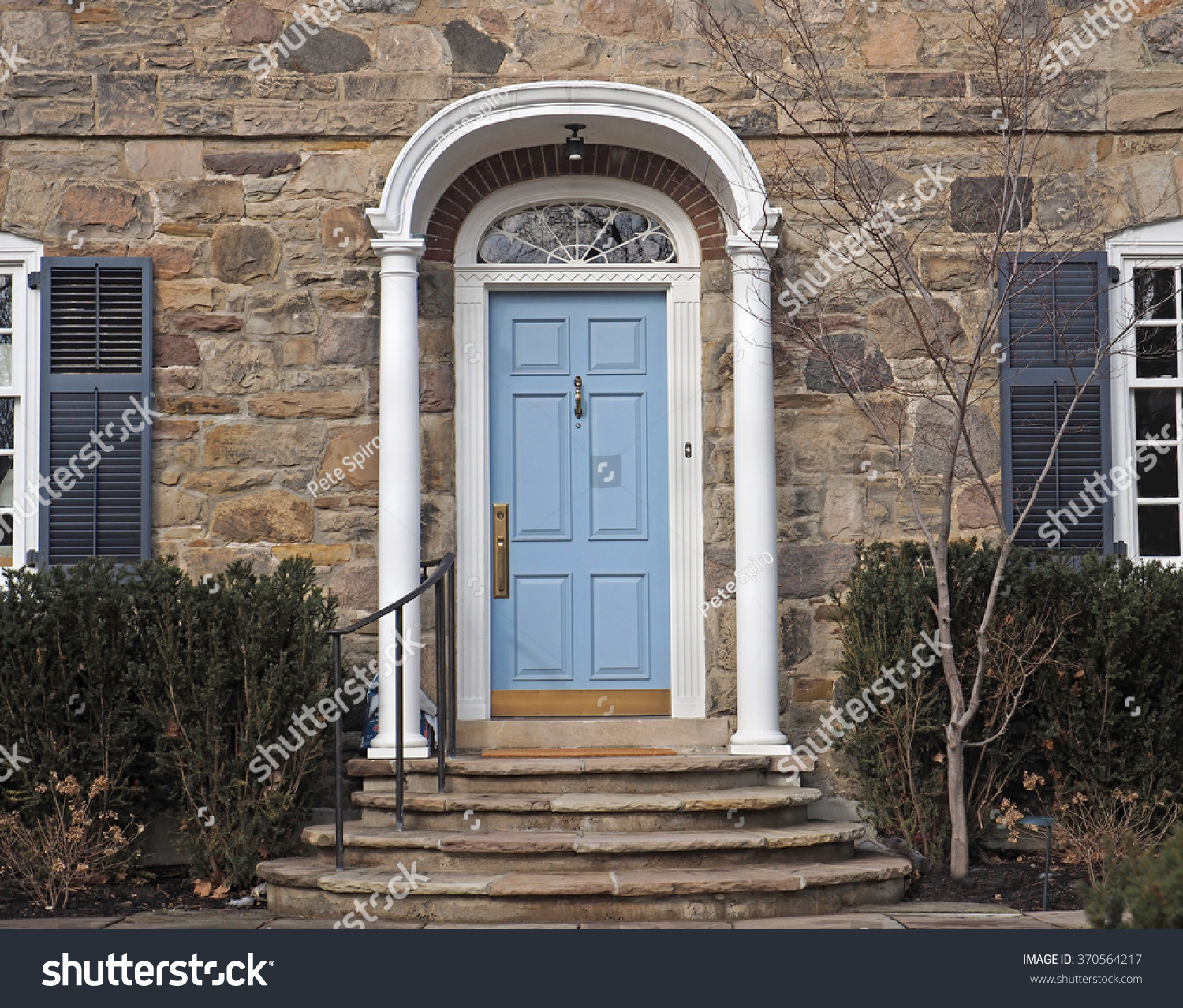 Stone faced house with portico around front door stock for Stone faced houses
