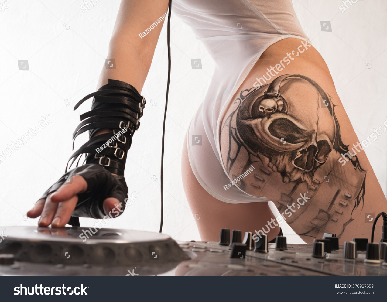 A girl with a beautiful ass plays electronic music mixer