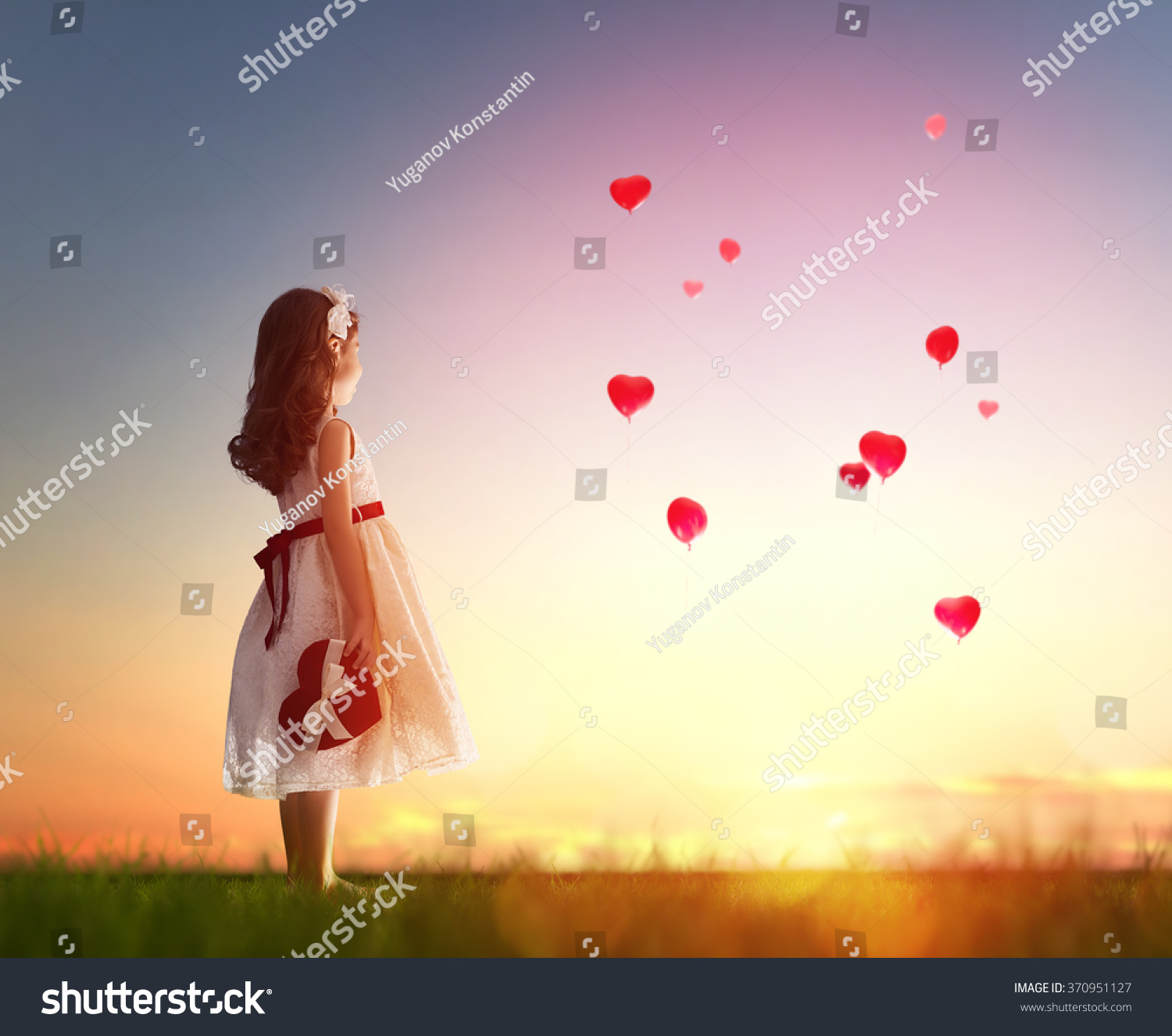 Sweet child girl looking at red balloons Balloons in shape of heart flying in the sunset sky Wedding Valentine love concept