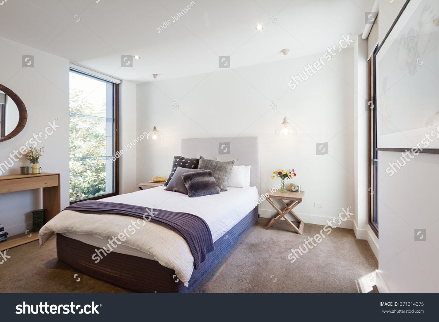 luxury interior designed bedroom with comfy pillows and throw rug and pendant lights