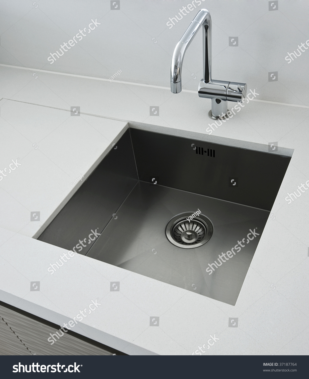 stock photo detail of a rectangular designer kitchen sink with chrome water tap 37187764