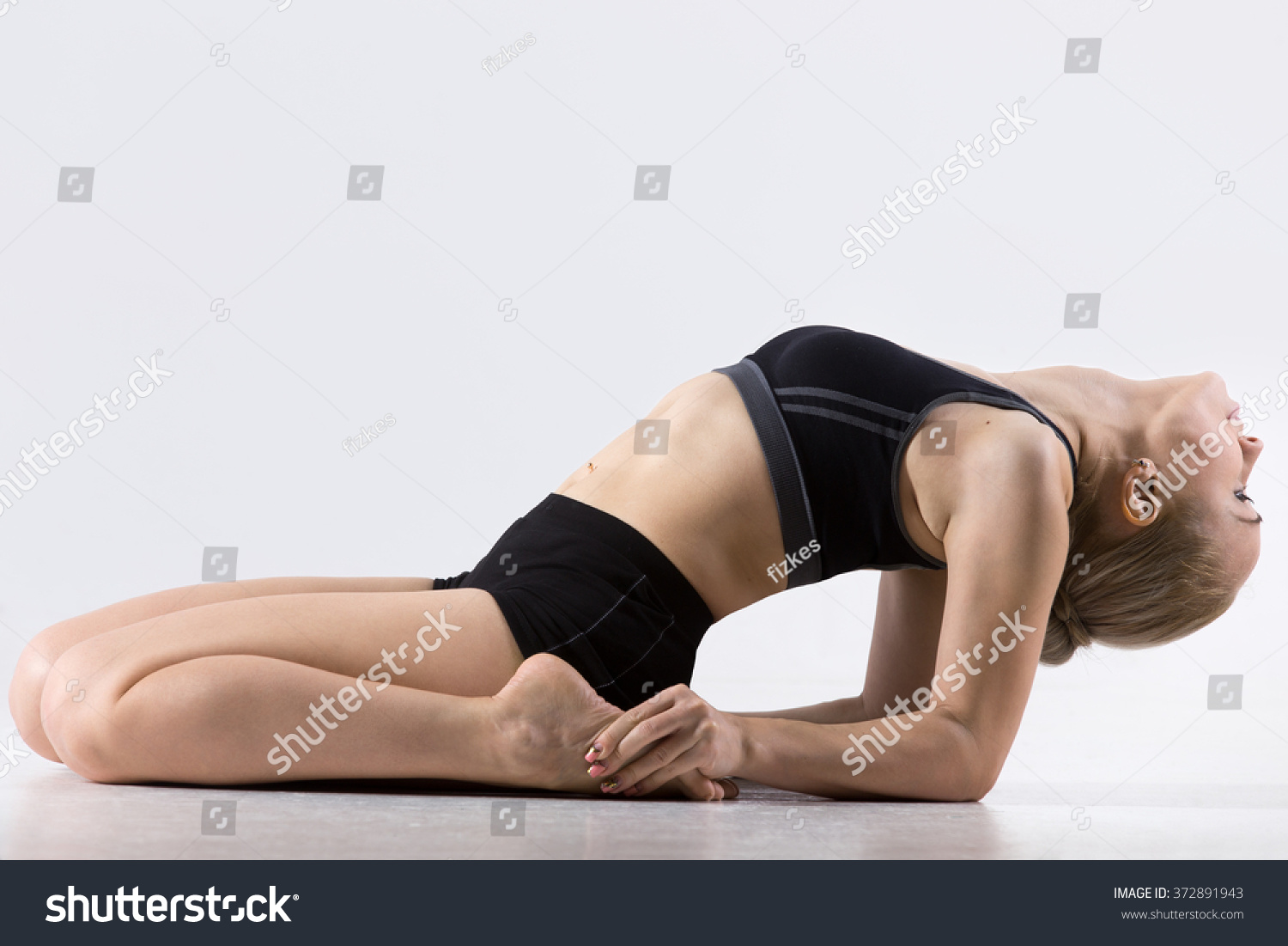 Sporty beautiful young woman practicing yoga doing Reclining Hero Pose - variation of Virasana or : reclining lotus position - islam-shia.org
