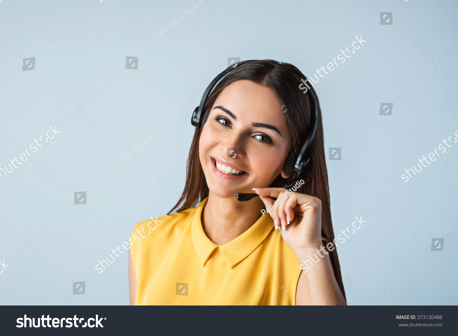 Photo of beautiful young call center operator standing near gray background. Woman with headphones looking at camera and smiling #373130488
