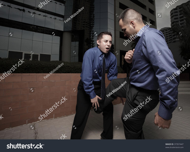 Businessman Kicking Other Businessman Groin Stock Photo