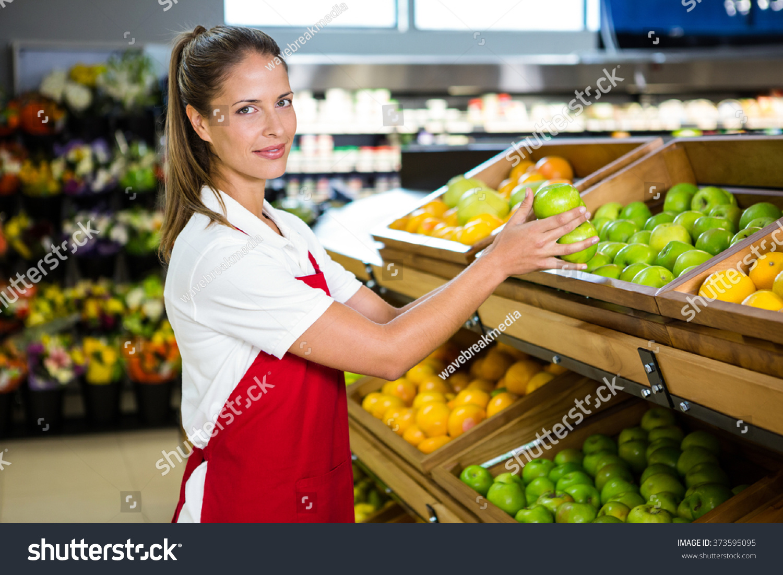 portrait female worker taking fruit grocery stock photo  portrait of female worker taking fruit in grocery store