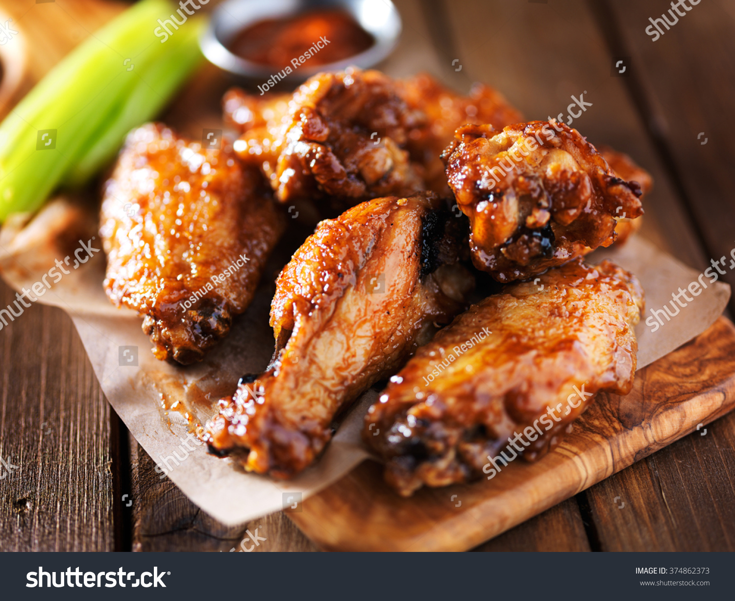 barbecue chicken wings close up on wooden tray shot with selective focus #374862373