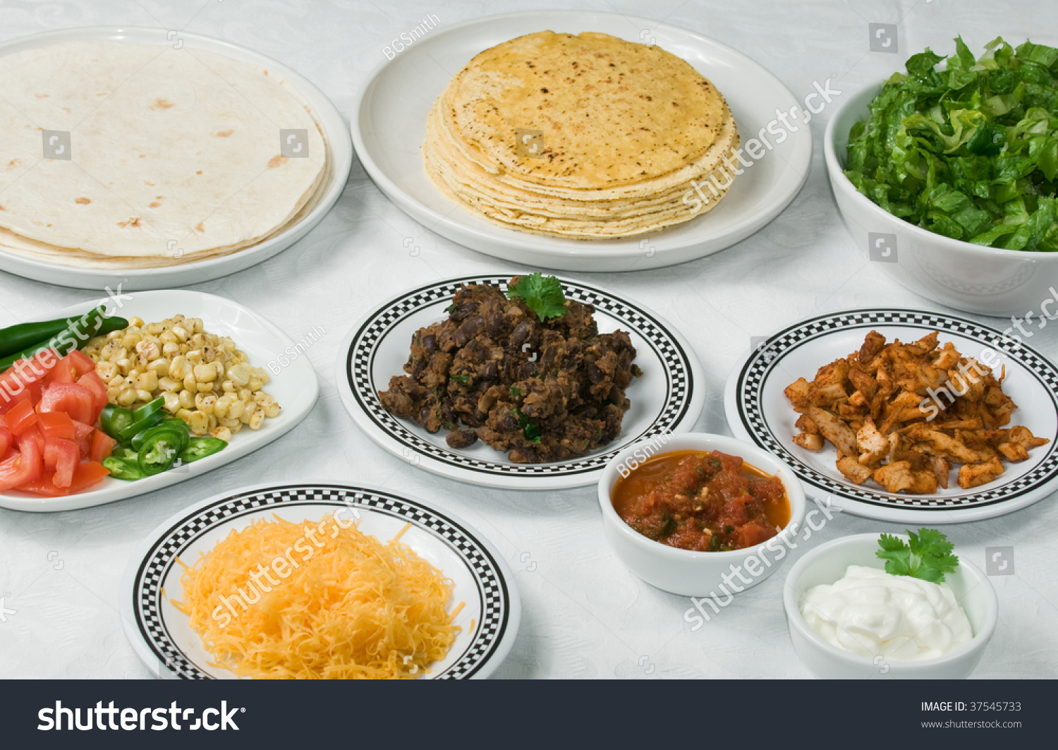 Dinner table with mexican food - Table Set With Mexican Ingredients For Taco Or Burrito Dinner