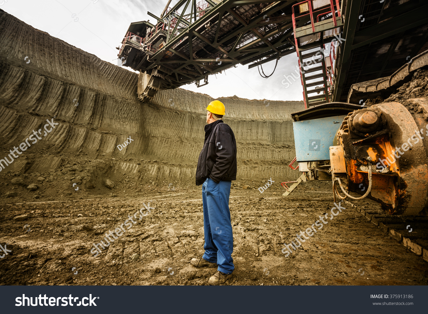 Coal mine worker with a helmet on his head standing in front of huge drill machine and looking at it Rear view