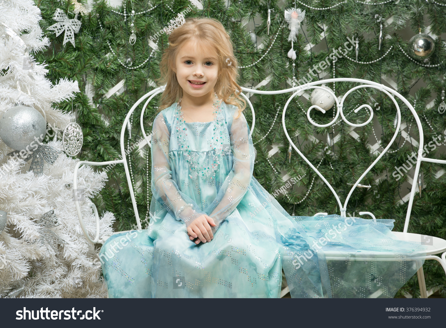 Happy little girl in a suit of the snow queen is sitting alone and smile near