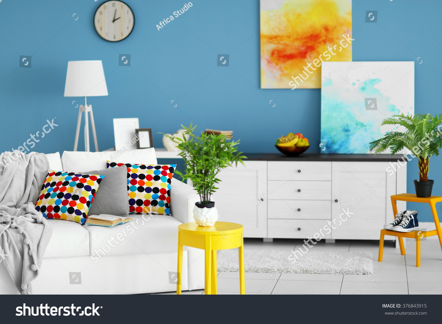 Living Room Interior With White Furniture And Green Plants Pictures On Blue Wall Background