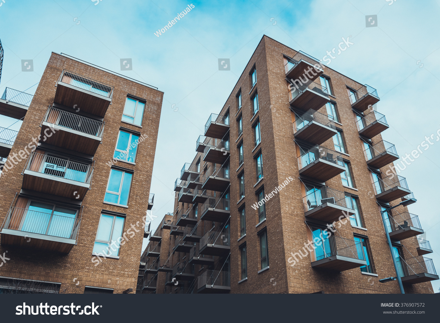 Extreme Wide Angle View Of Tall Brick Residential Apartment Buildings With  Tiny Balconies And Long Windows