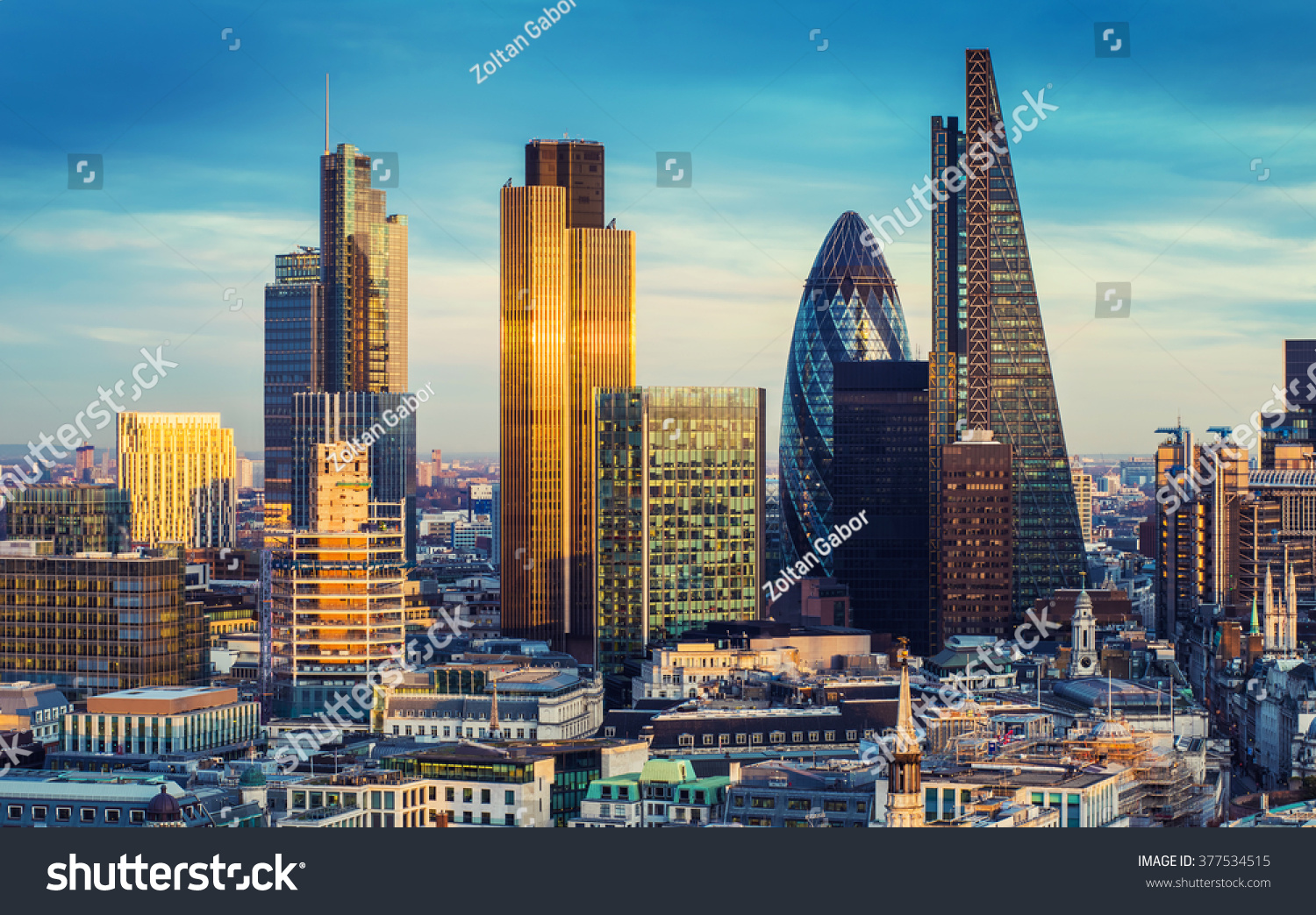 London, England - The bank district of central London with famous skyscrapers and other landmarks at sunset with blue sky - UK #377534515