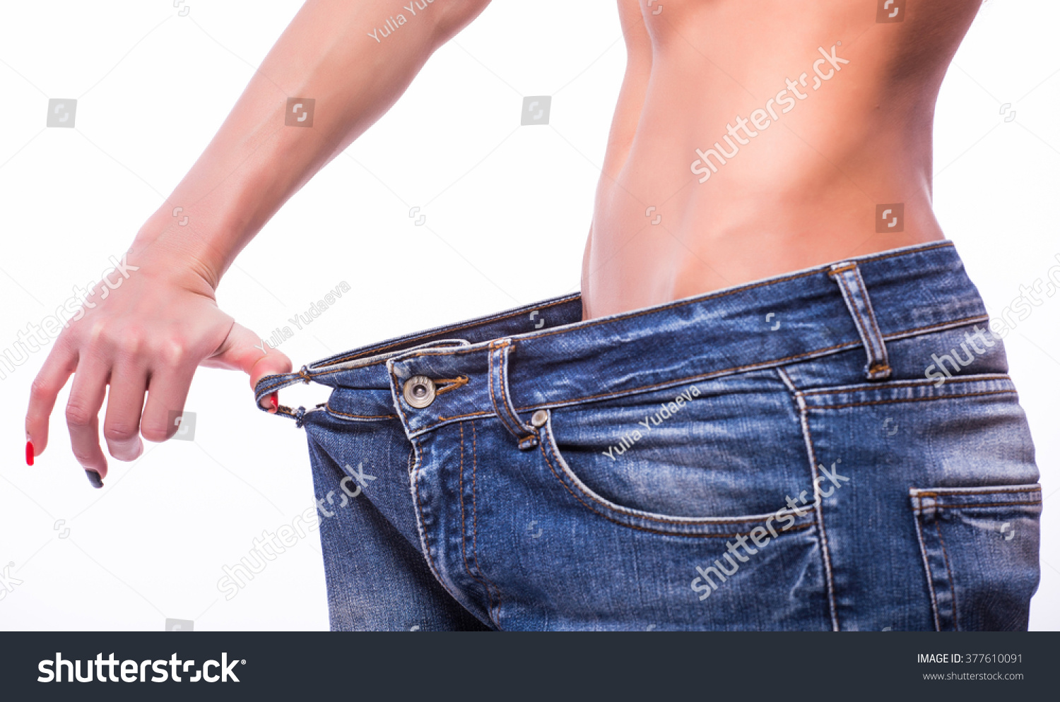 Background image too big - Young Fitness Woman Showing That Her Old Jeans Became Too Big For Her Over White Background