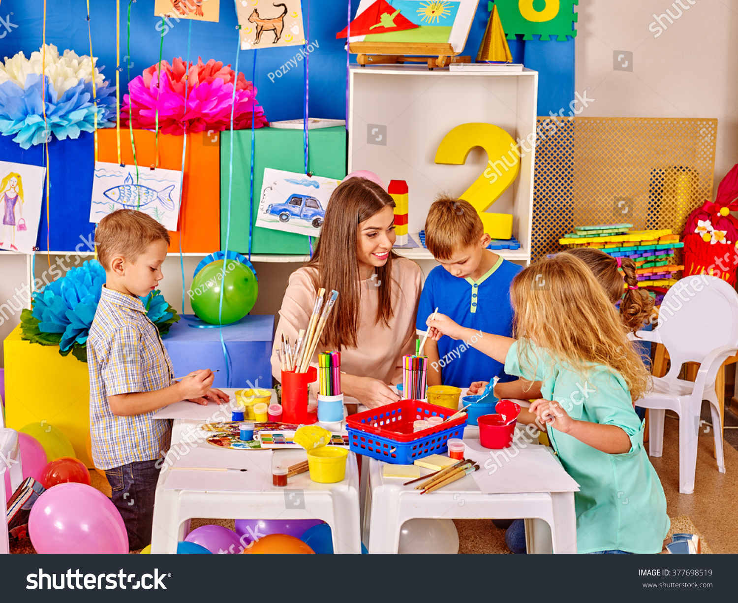 group of kids with female teacher painting together in kindergarten